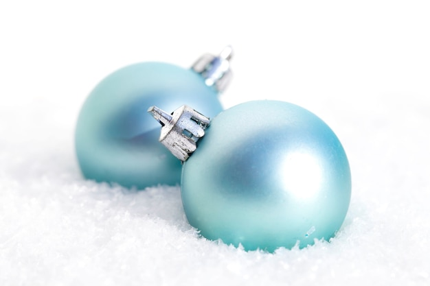 Close de lâmpadas de natal azuis na neve em frente a um fundo desfocado Foto gratuita