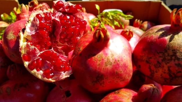 Close de romãs frescas em uma caixa sob a luz do sol no bazar Foto gratuita