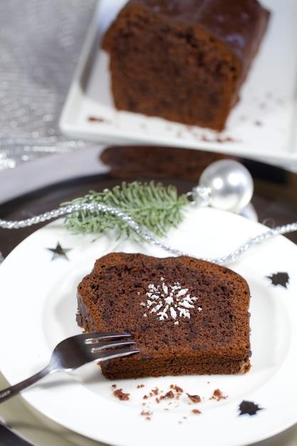 Close de um brownie em um prato branco ao lado da decoração de natal prata Foto gratuita