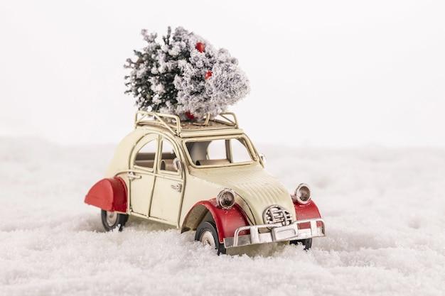 Close de um carrinho de brinquedo antigo com uma árvore de natal no telhado na neve Foto gratuita
