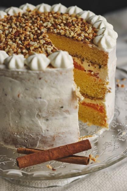 Close de um delicioso bolo branco de natal fatiado com nozes e tangerina Foto gratuita