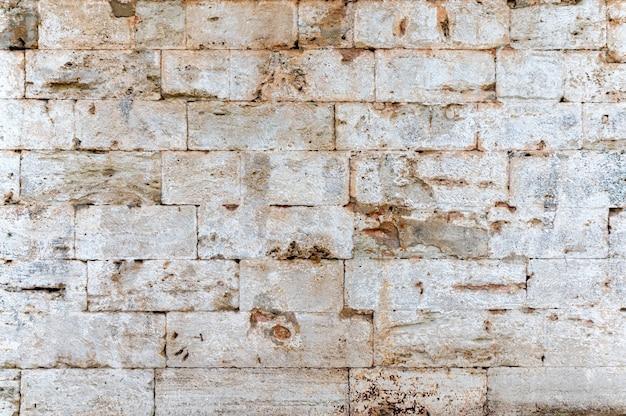 Close de um fundo de textura de parede de pedra de tijolos brancos antigos Foto Premium