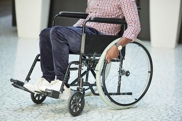Close de um homem africano com deficiência, andando em uma cadeira de rodas ao longo do corredor Foto Premium