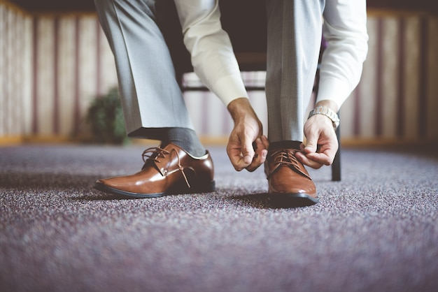Close de um homem amarrando os sapatos e se preparando para uma reunião de negócios Foto gratuita