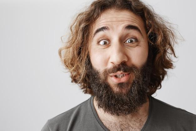 Close de um homem do oriente médio surpreso e otimista parecendo fascinado Foto gratuita