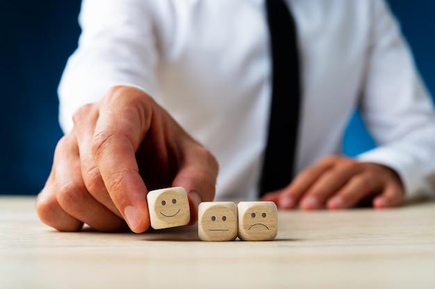 Close de um homem escolhendo dados de madeira com uma cara sorridente entre três opções Foto Premium
