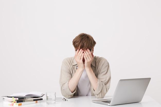 Close de um jovem estudante alegre do sexo masculino com aparelho ortodôntico usa um estudo de camisa bege usando um laptop e notebooks sentados à mesa isolada sobre a parede branca Foto gratuita