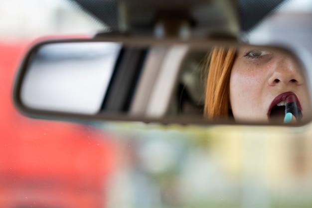 Close de um motorista de mulher jovem ruiva corrigindo sua maquiagem com batom vermelho escuro, olhando no espelho retrovisor do carro atrás do volante de um veículo. Foto Premium