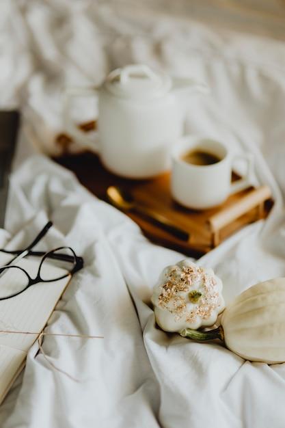 Close de um notebook, uma xícara de café e abóboras brancas na cama Foto Premium