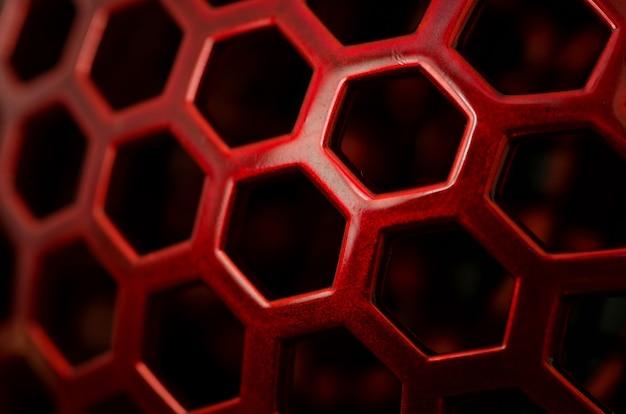 Close de um padrão vermelho com orifícios hexagonais Foto gratuita