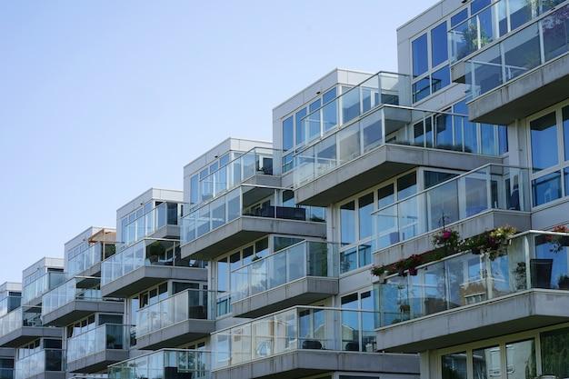Close de um prédio de apartamentos com varandas da vila. fundo das janelas e varandas de um edifício de vidro de vários andar. Foto Premium