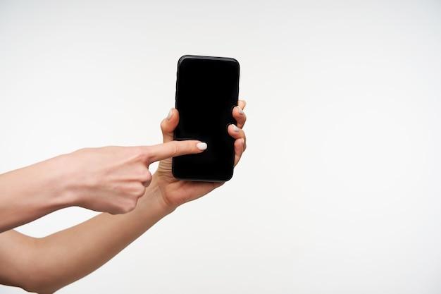 Close de um telefone celular preto moderno sendo segurado pela mão de uma mulher levantada e deslizando na tela com o dedo indicador em pé sobre o branco Foto gratuita