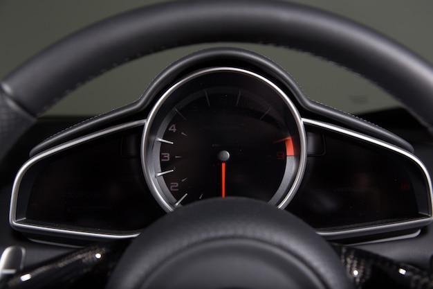 Close de um velocímetro e o volante de um carro moderno sob as luzes Foto gratuita