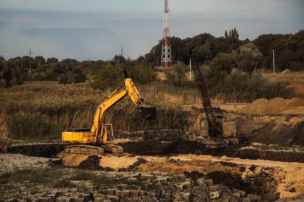 Close de uma construção em andamento com trilhos e uma escavadeira em um terreno abandonado Foto gratuita