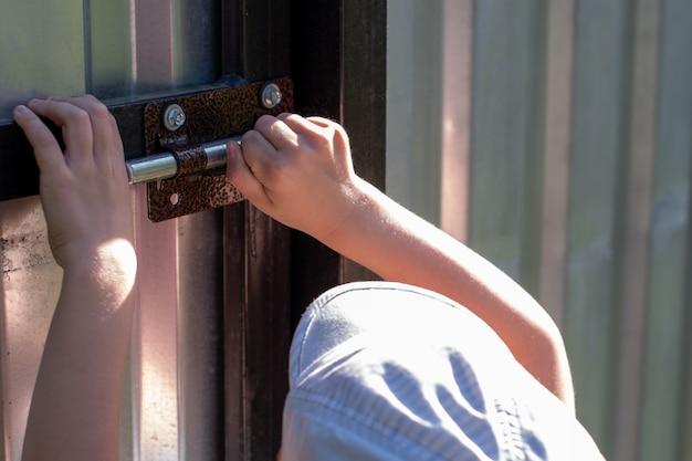 Close de uma criança abrindo o portão de ferro Foto Premium
