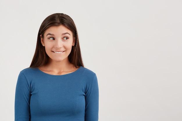 Close de uma jovem brincalhona e feliz com cabelo comprido usando manga comprida azul marinho mordendo o lábio e exibindo sinal de silêncio isolado sobre uma parede branca Foto gratuita