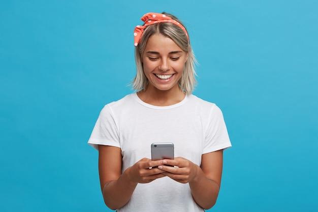 Close de uma jovem loira bonita e alegre usando uma camiseta branca Foto gratuita