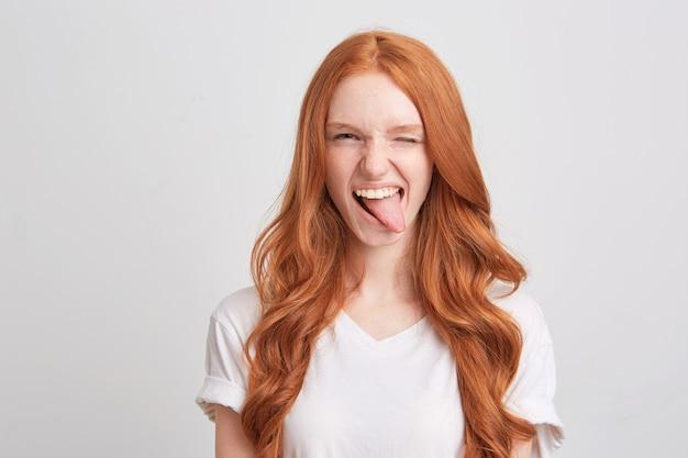 Close de uma jovem ruiva bonita com cabelo comprido ondulado e sardas usa uma camiseta triste e olha para a frente isolada sobre uma parede branca Foto gratuita