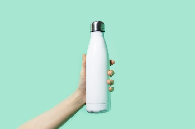Close de uma mão feminina segurando uma garrafa de água térmica ecológica reutilizável Foto Premium