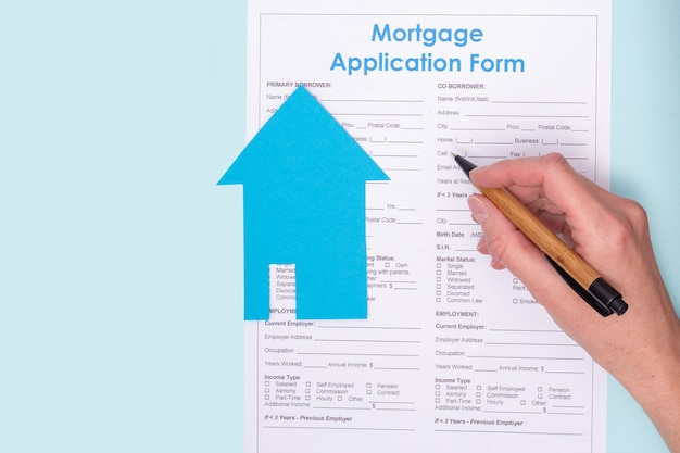 Close de uma mão segurando uma caneta sobre um contrato de pedido de hipoteca de casa com uma casa azul de papel em um documento, vista superior Foto Premium