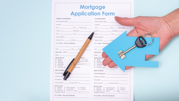 Close de uma mão segurando uma chave em uma casa de papel azul sobre um pedido de hipoteca e uma caneta, vista superior Foto Premium