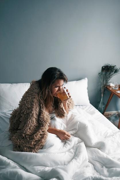 Close de uma menina doente tomando seu remédio na cama Foto Premium