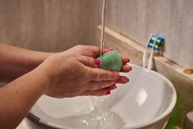 Close de uma mulher lavando as mãos com uma barra de sabão sob as luzes em um banheiro Foto gratuita