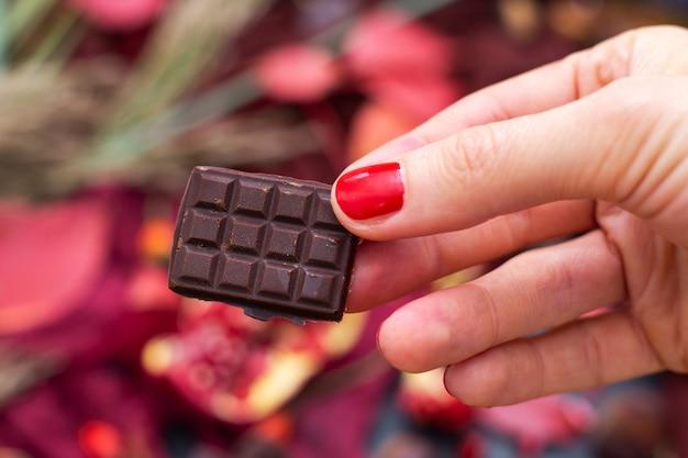 Close de uma mulher segurando um pedaço de chocolate vegan cru com um fundo desfocado Foto gratuita