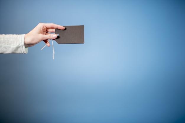 Close de uma mulher segurando uma etiqueta em branco com um fundo azul - ótimo para escrever texto Foto gratuita