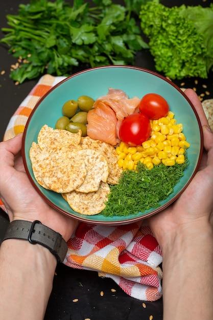 Close de uma pessoa segurando uma tigela de salada com salmão, biscoitos e vegetais sob as luzes Foto gratuita