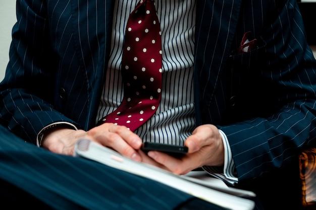 Close de uma pessoa vestindo um terno e segurando um telefone com um notebook Foto gratuita