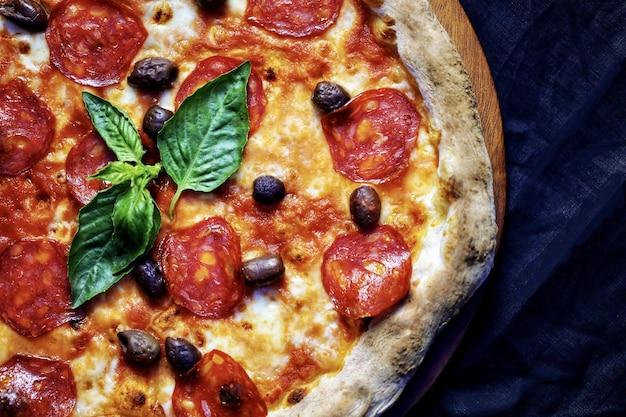 Close de uma pizza de calabresa em uma placa de madeira sob as luzes Foto gratuita