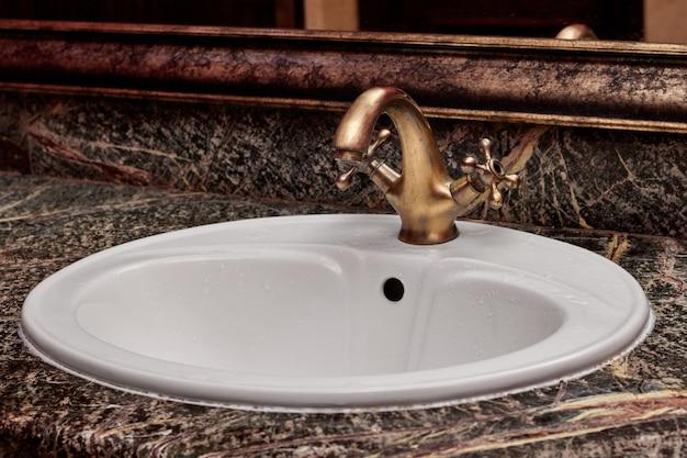 Close de uma torneira de latão com alças quentes e frias em uma pia branca em um banheiro Foto gratuita