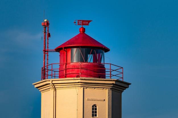 Close de uma torre vermelha e branca atrás de um céu azul Foto gratuita