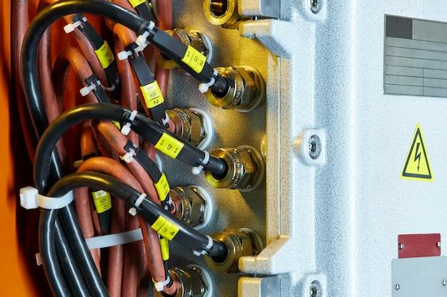 Close do cabo conectado ao quadro de distribuição usando porcas, nas placas do quadro de distribuição para preencher as informações Foto Premium