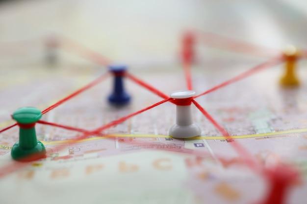 Close do mapa marcado com trajetórias de movimento do fio vermelho. plano de rua com botões formando rota. rota de construção de pedestres pela cidade. conceito de navegação Foto Premium