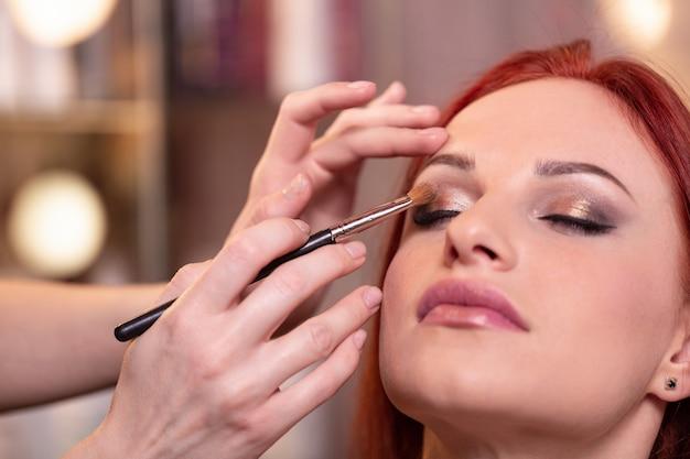 Close do rosto de mulher jovem e bonita com maquiagem de beleza Foto Premium