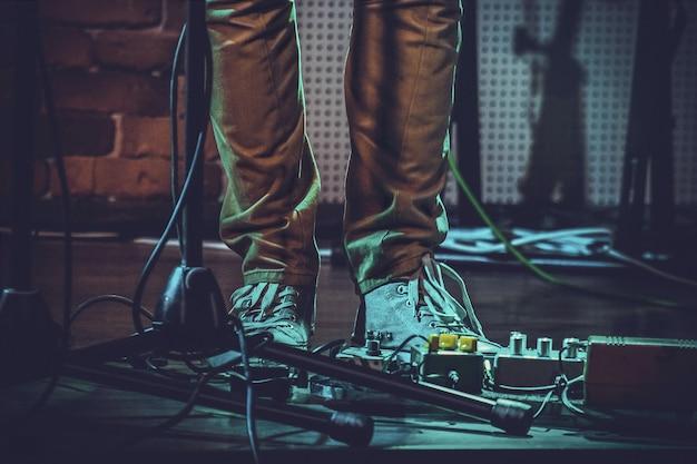 Close dos pés de uma pessoa perto de pedais de guitarra e um pedestal de microfone sob as luzes Foto gratuita