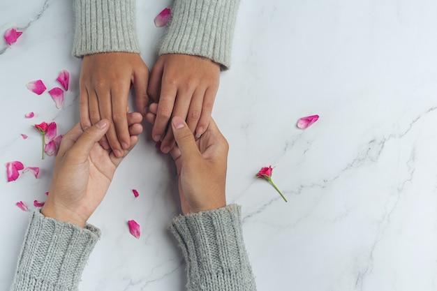Close em dois jovens amantes de mãos dadas em uma mesa. Foto gratuita