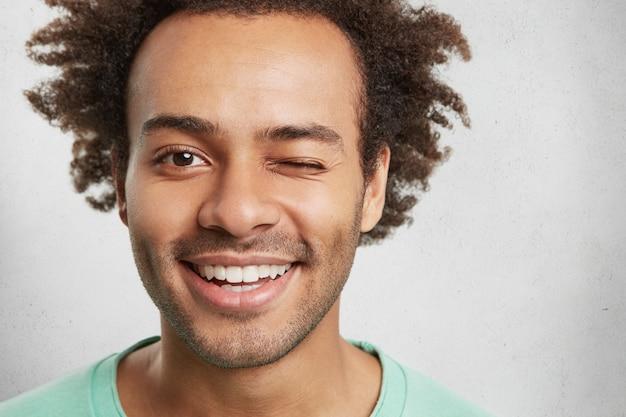 Close extremo de mestiço. homem bonito tem um penteado moderno, sorri agradavelmente e pisca os olhos Foto gratuita