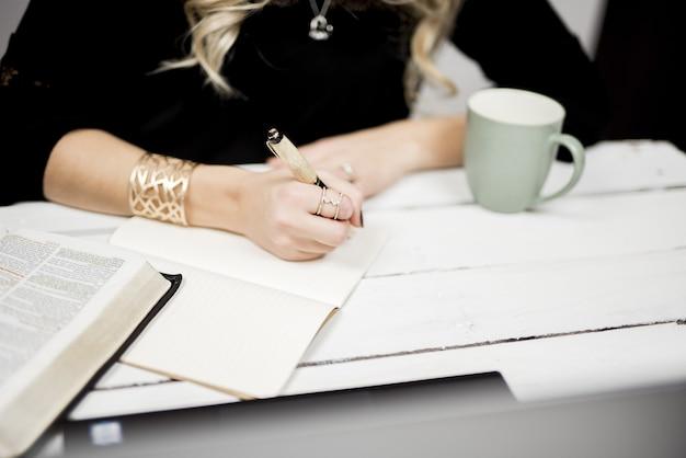 Close seletivo de uma pessoa fazendo anotações em um livro Foto gratuita