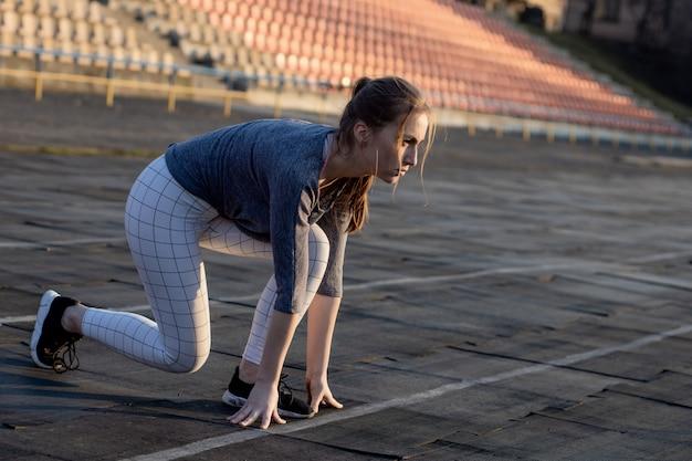 Close-up atleta enquanto treinava, preparando-se para correr na pista de corrida, começando no estádio Foto Premium