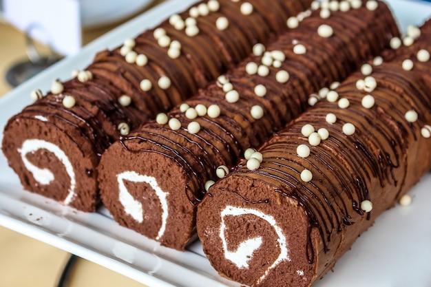 Close-up belo rolo de batata doce de chocolate no prato branco Foto Premium