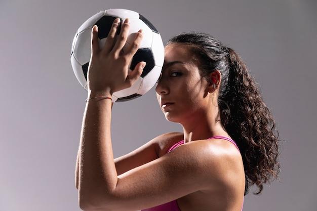 Close-up cabe mulher segurando bola de futebol Foto gratuita