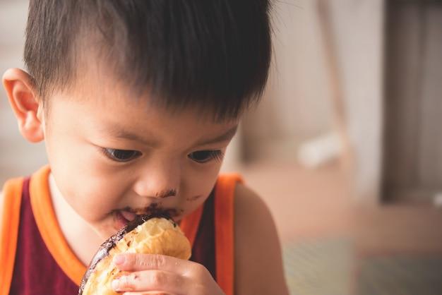 Close-up cara de garotinho faminto eaitng donut quente Foto gratuita