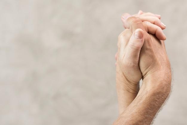 Close-up casal de mãos dadas com fundo desfocado Foto gratuita