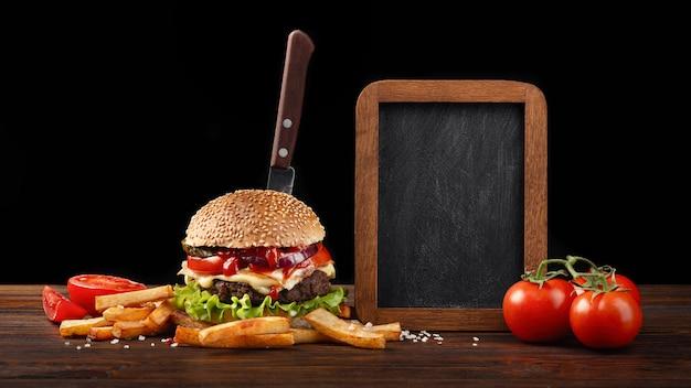 Close-up caseiro de hambúrguer com carne, tomate, alface, queijo, batatas fritas e placa de giz na madeira Foto Premium