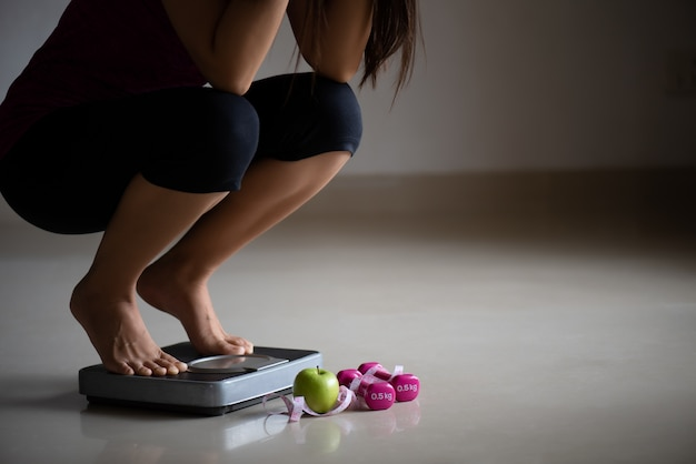 Close-up chateado perna feminina pisar pesar escalas com fita métrica. Foto Premium