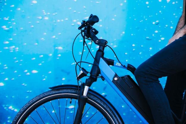 Close-up ciclista na e-bicicleta com fundo de aquário Foto gratuita
