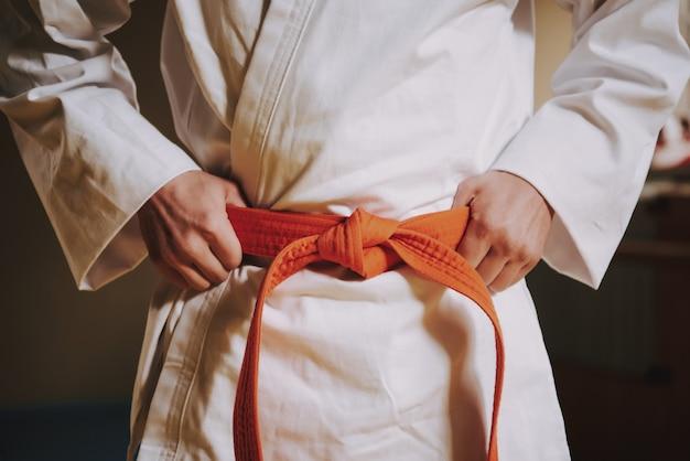 Close-up cinto vermelho no branco do lutador de artes marciais Foto Premium